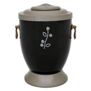 Juoda urna su rankenėlėmis ir blizgiu gėlės ornamentu